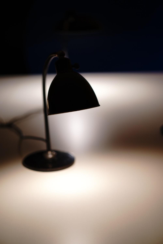 black desk lamp turned on in dim light