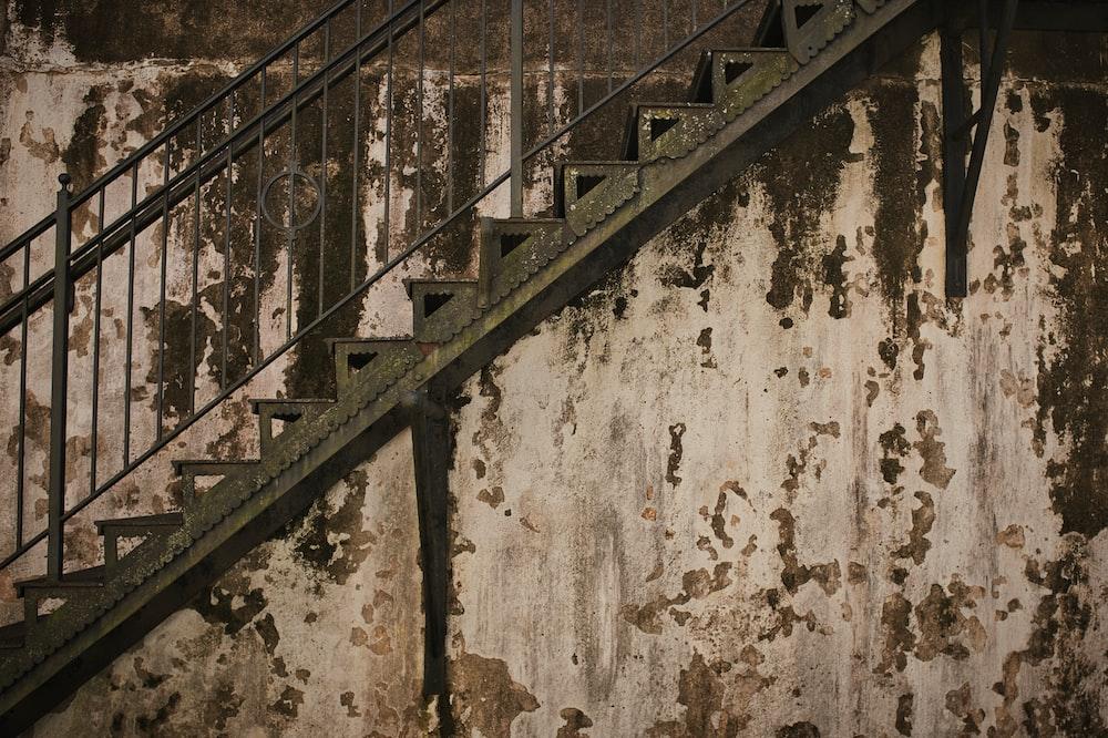 black metal railings on white concrete wall