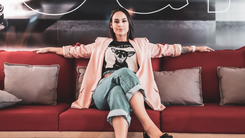 woman in black and white crew neck t-shirt sitting on red couch