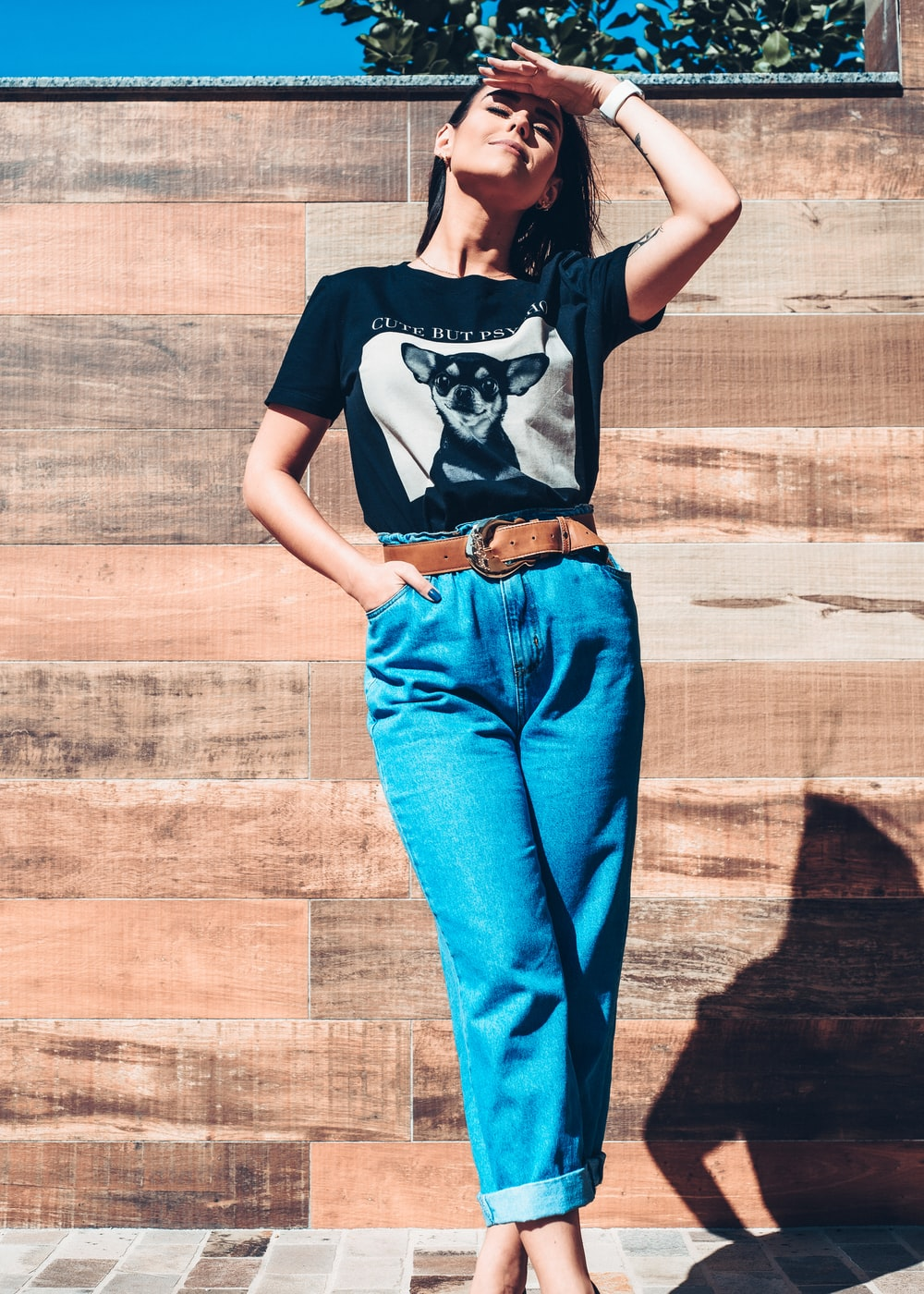 woman in black and white t-shirt and blue denim jeans standing on brown wooden floor