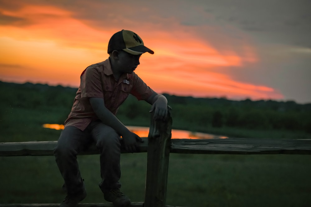man in brown jacket and blue denim jeans sitting on brown wooden fence during sunset
