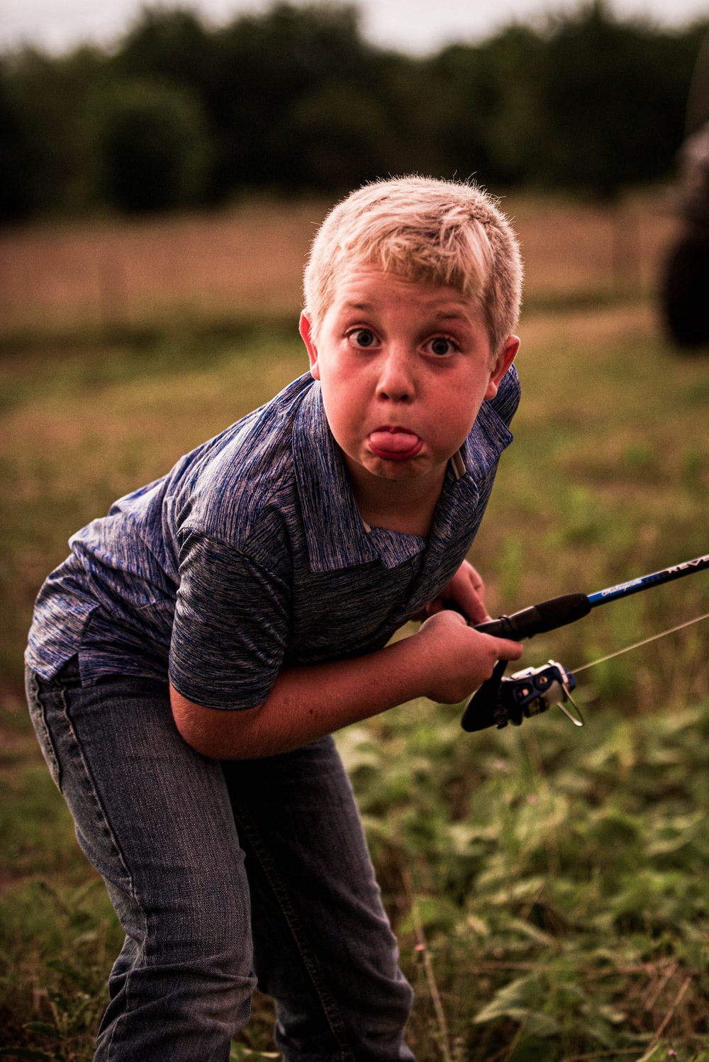 boy in gray and black stripe polo shirt and blue denim jeans holding black fishing rod