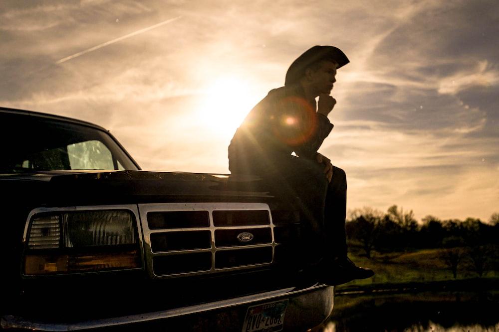 man in black jacket and black cap sitting on black car hood during daytime