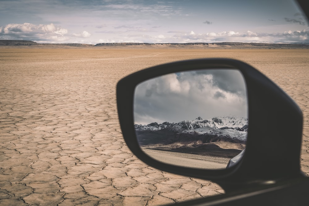 car side mirror with reflection of clouds on water