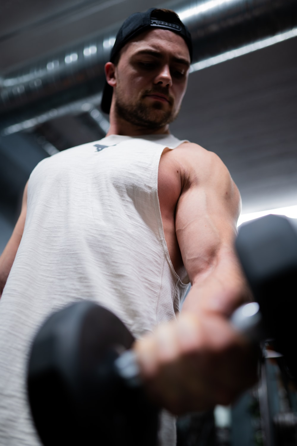 man in white tank top holding black and silver dumbbell