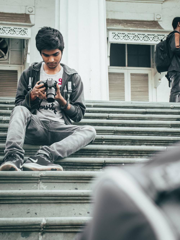 man in gray hoodie sitting on stairs