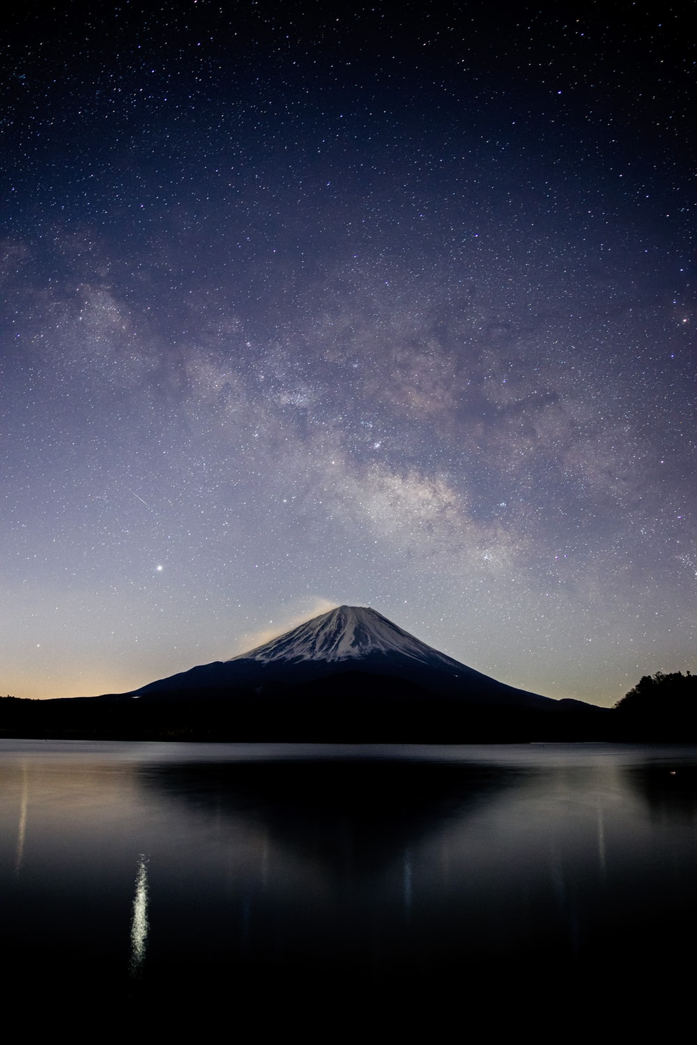snow covered mountain near lake under starry night