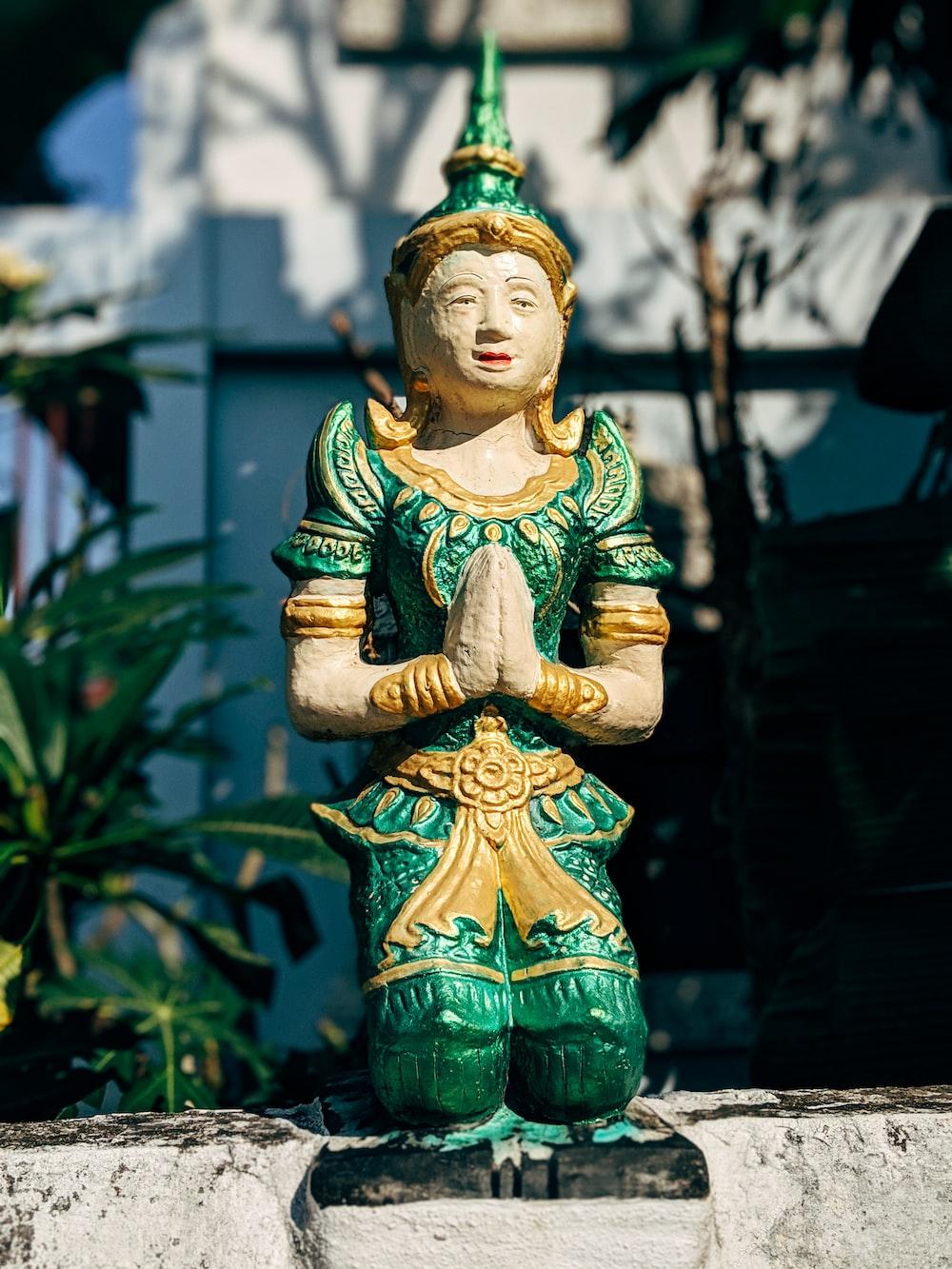 green and yellow ceramic buddha figurine