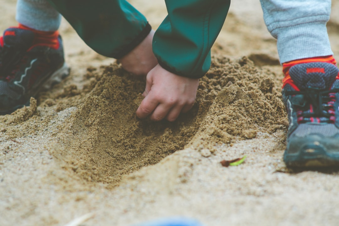 Young boy digs with his hands in the sand at the playground. Made with Canon 5d Mark III and analog vintage lens, Leica Elmarit-R 2.8 135mm (Year: 1987)