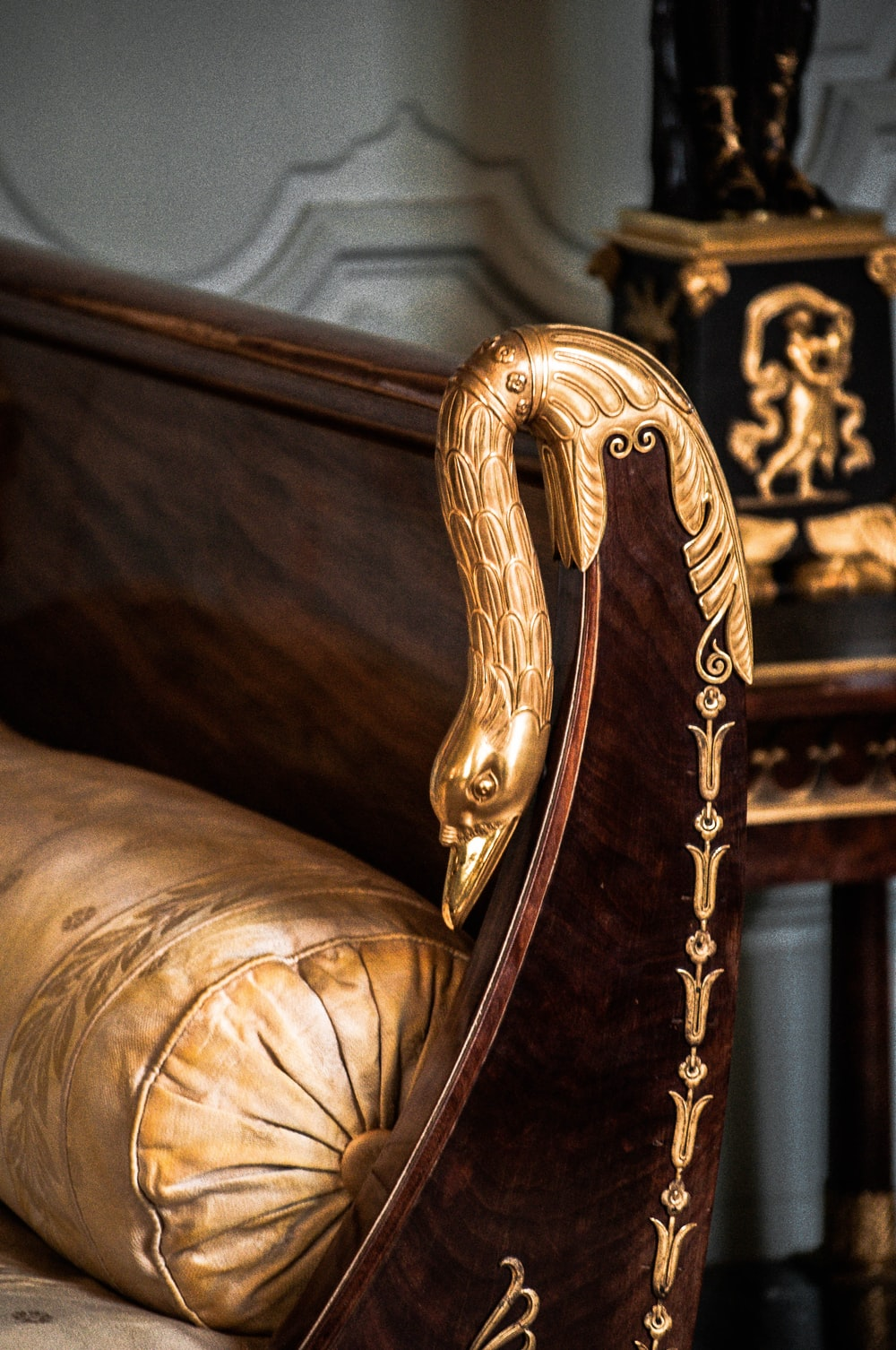 brown wooden framed white padded armchair