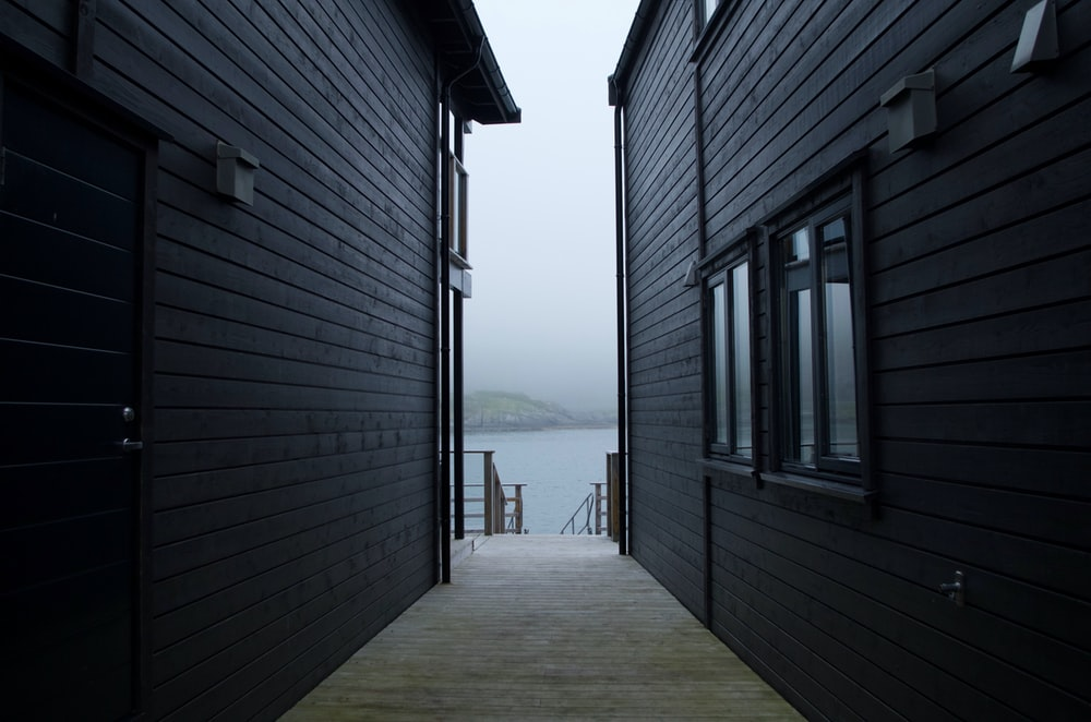 gray wooden house near sea during daytime