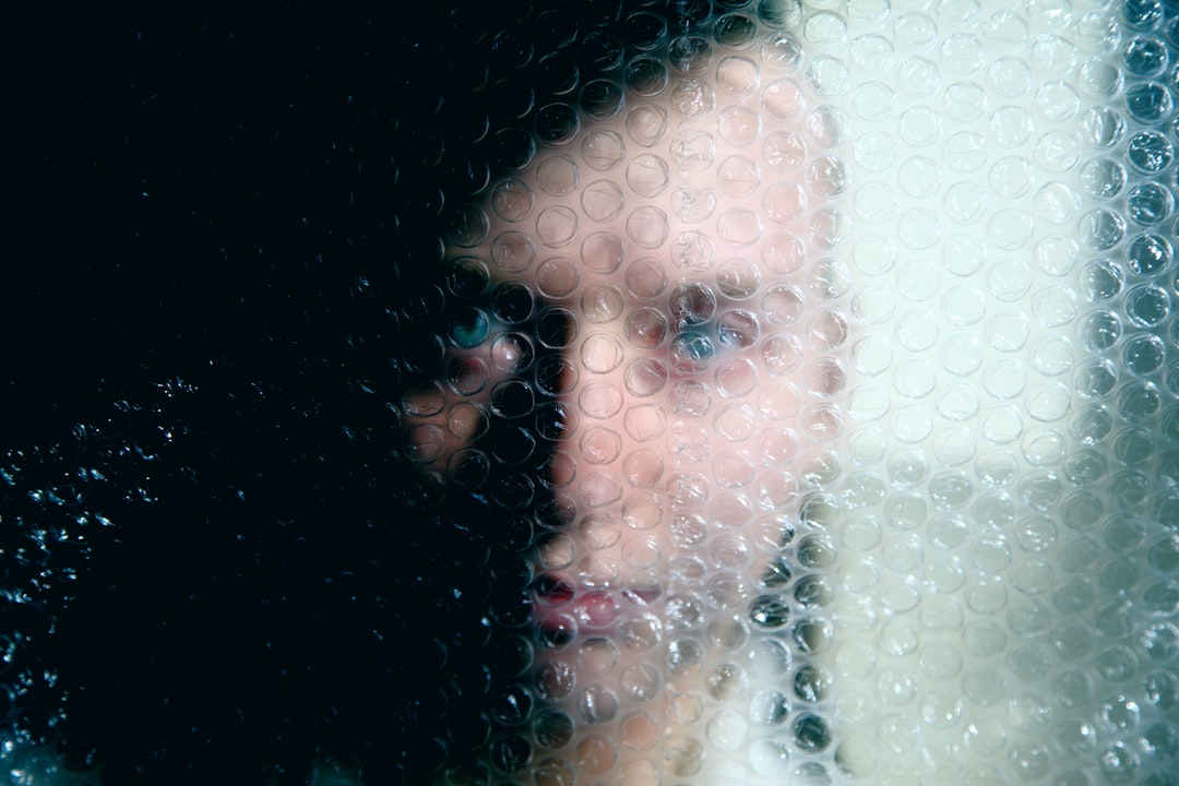 Portrait of a young woman obscured behind plastic bubble wrap.