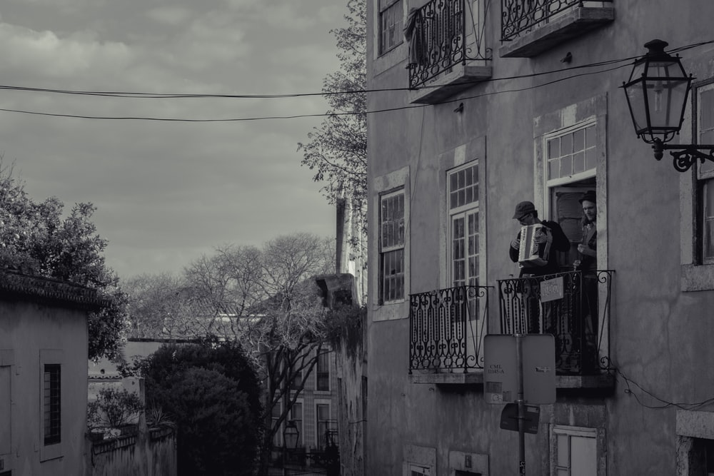 grayscale photo of man in black jacket standing on balcony