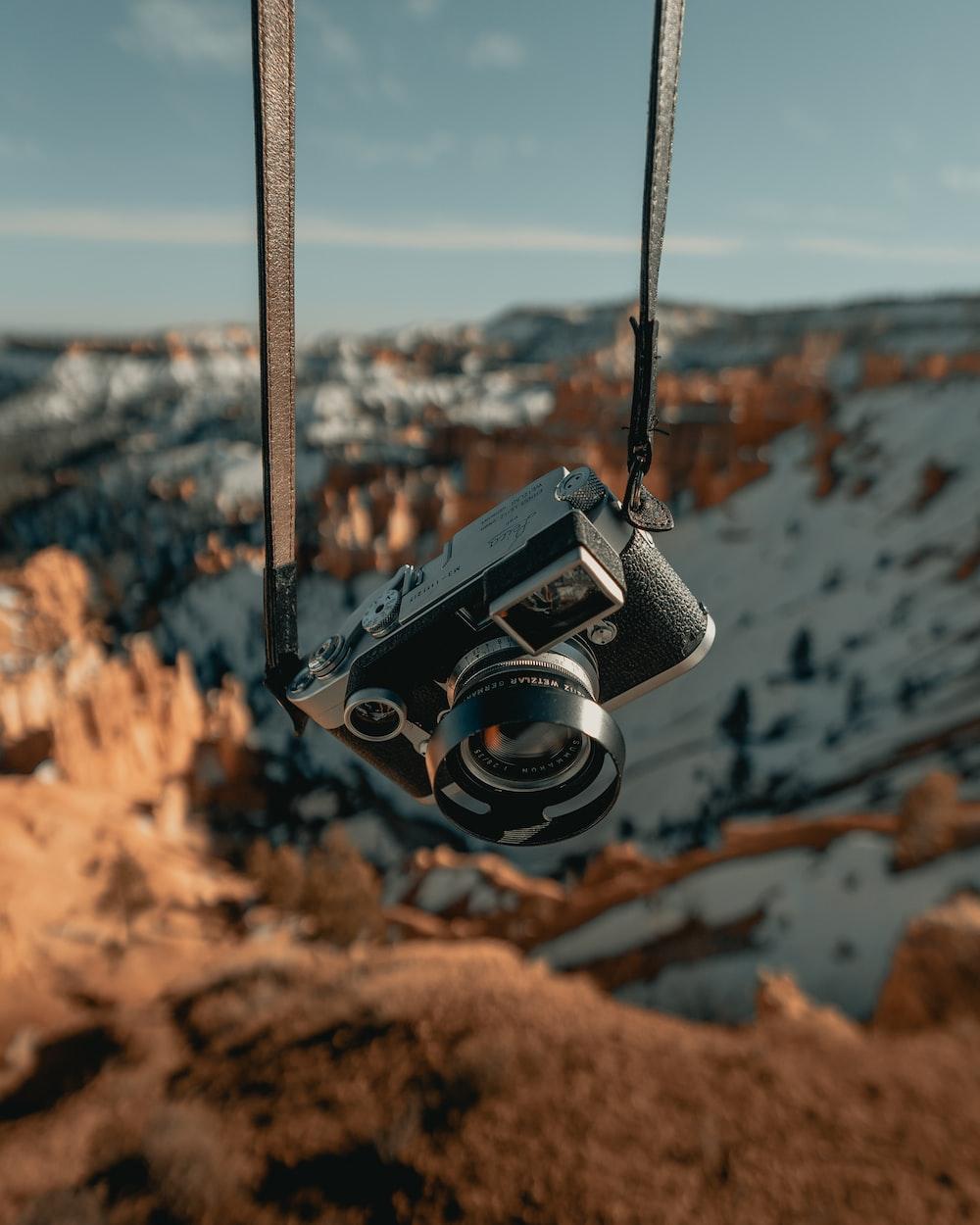 black and silver dslr camera hanging on black rope