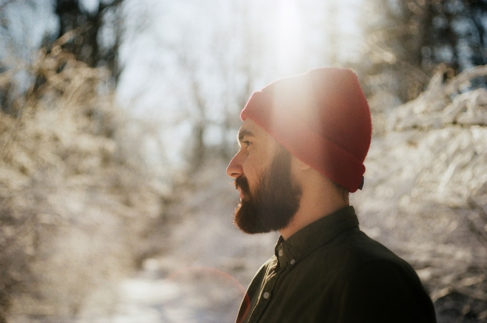 man in red knit cap and black jacket