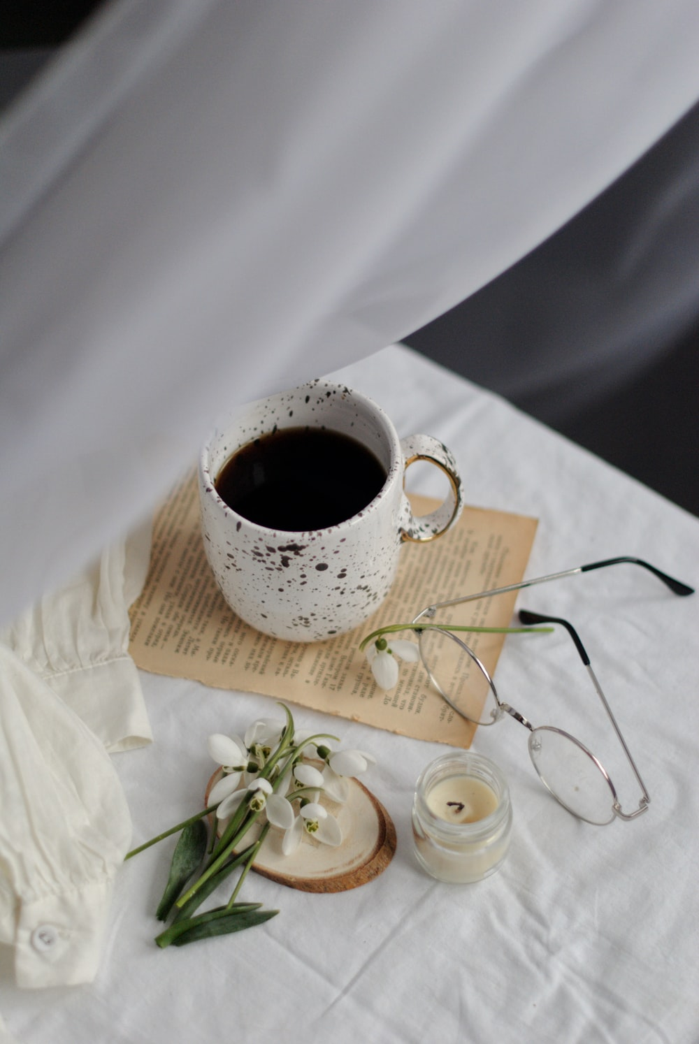 white ceramic mug on brown wooden coaster beside white flowers