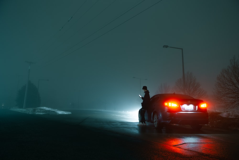 man in black jacket and black pants standing beside red car during night time