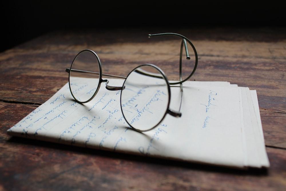 silver framed eyeglasses on white printer paper
