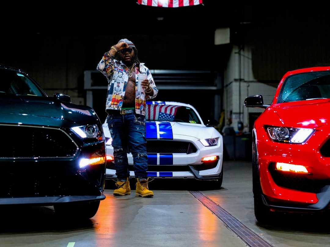 A music artist wearing a shirt imprinted with the faces of Narcos, performs while surrounded by Ford Mustangs.