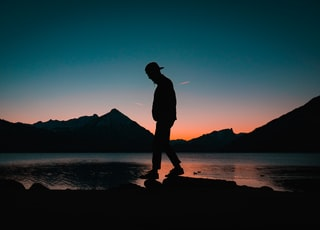 silhouette of man standing on seashore during night time