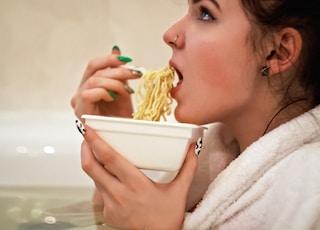 woman holding white ceramic bowl with yellow pasta