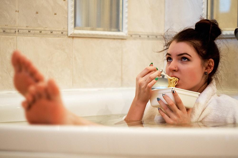 girl in bathtub holding white ceramic mug