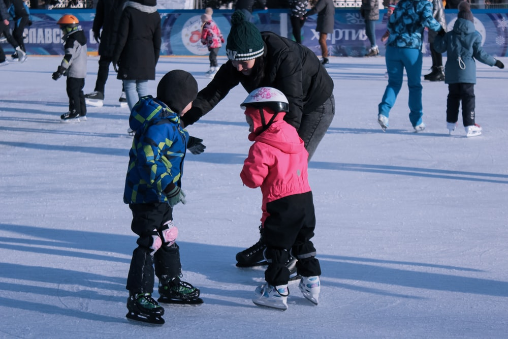 2 children in red jacket and black pants playing ice hockey
