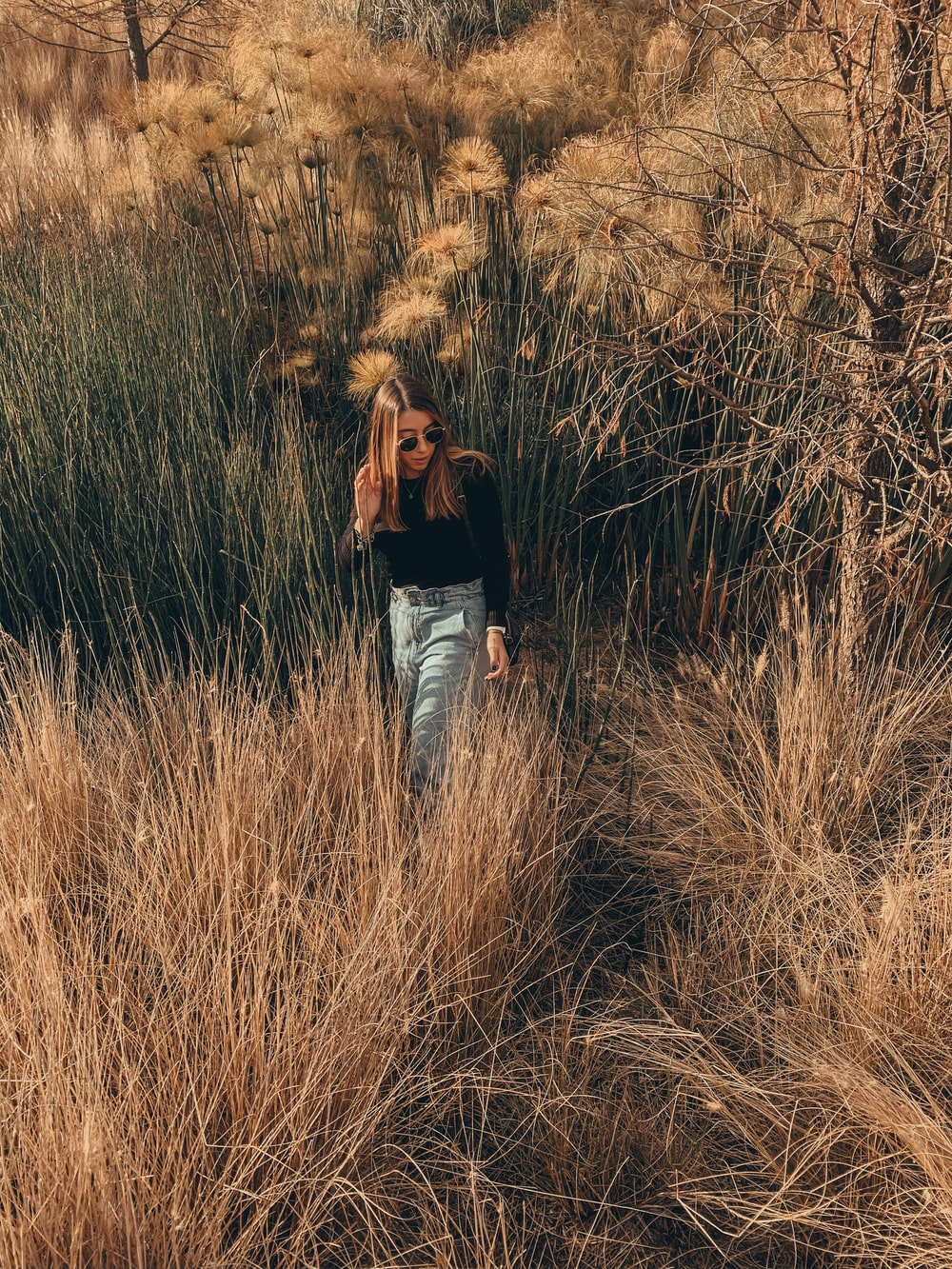 woman in black long sleeve shirt and blue denim jeans standing on brown grass field during