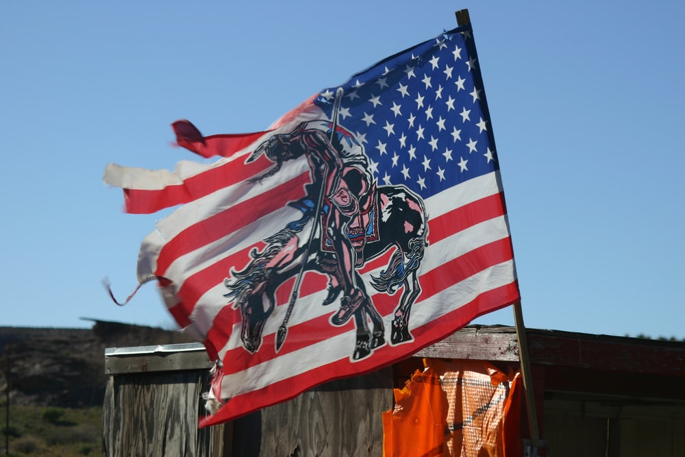 us a flag on brown wooden fence