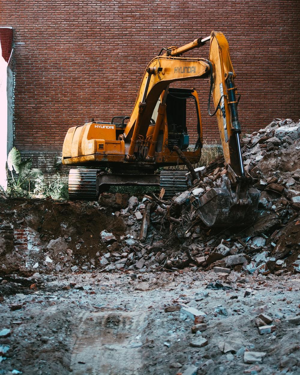 yellow excavator beside brown brick wall