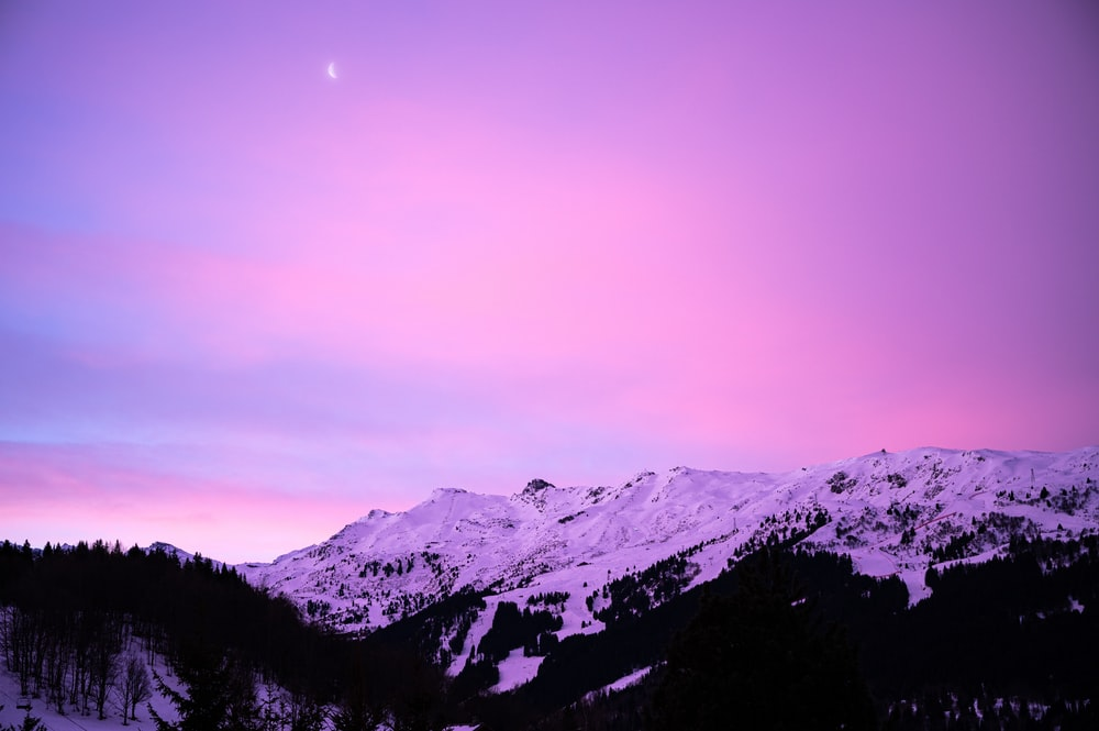 snow covered mountain under purple sky