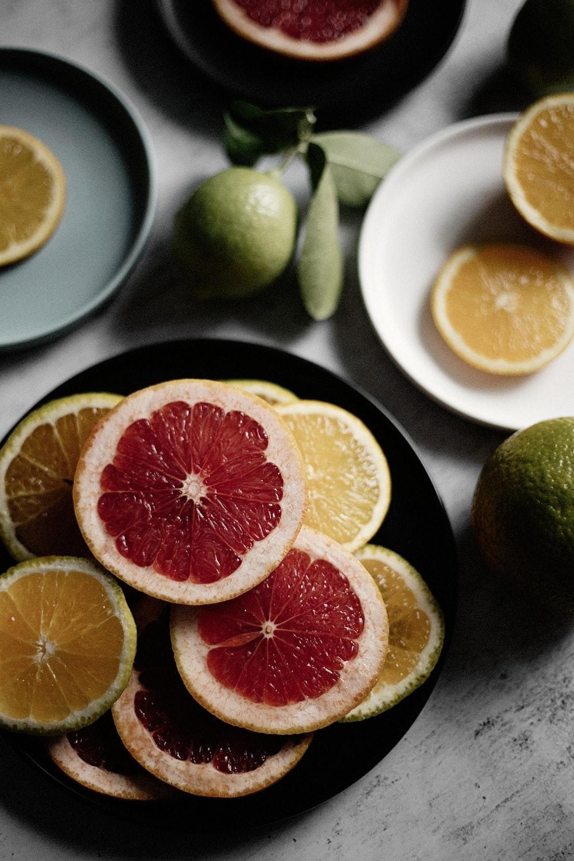 sliced orange fruit on black ceramic plate