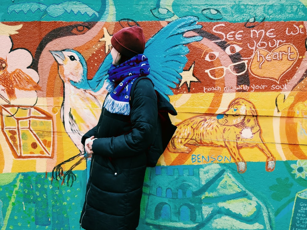 man in black jacket and blue scarf standing beside wall with graffiti