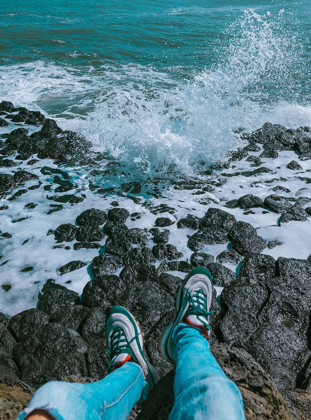 person in green and white sneakers standing on rocky shore during daytime
