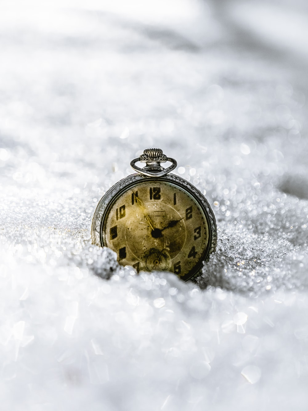 gold and black round pocket watch on snow