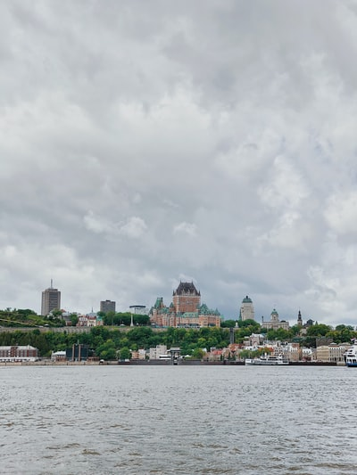 city buildings near body of water under cloudy sky during daytime