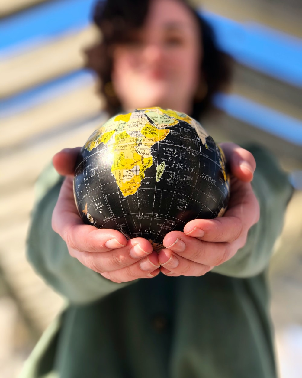 person holding yellow and black desk globe