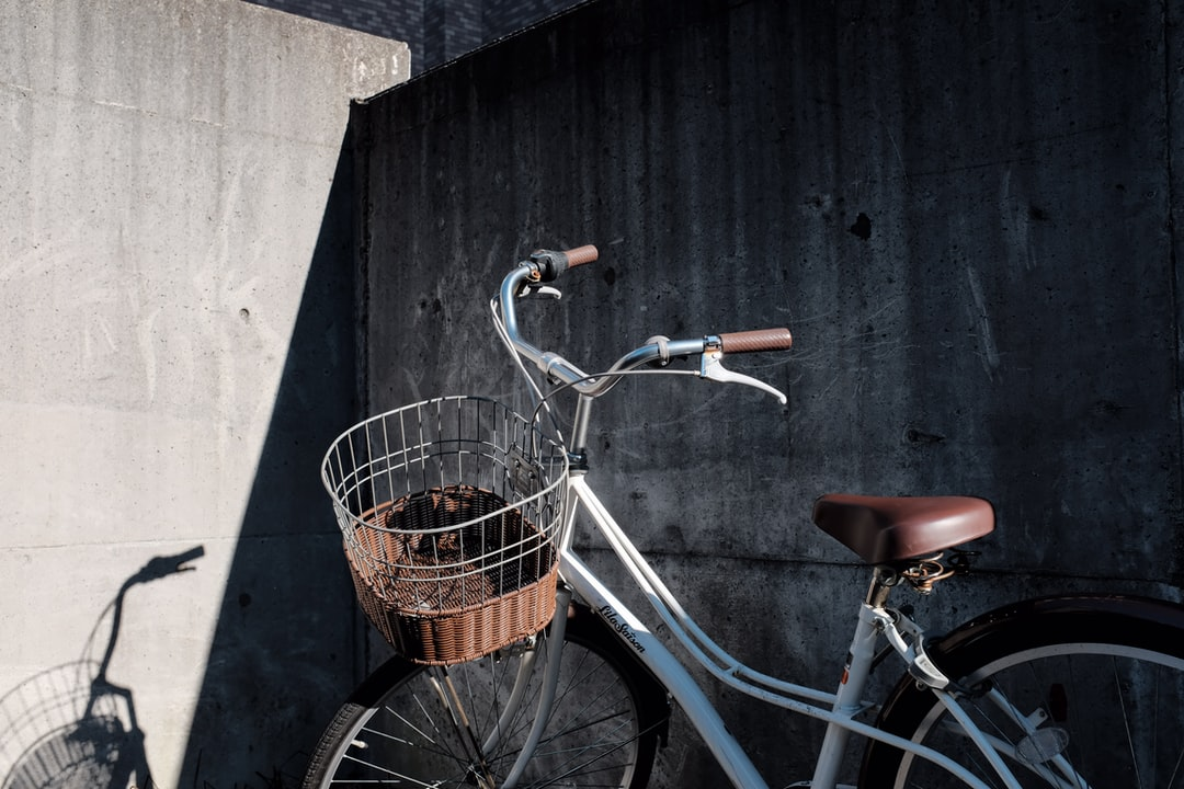 Blue City Bike With Basket On Black Wooden Wall - unsplash