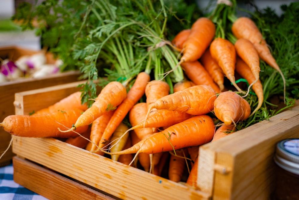 orange carrots on brown wooden crate