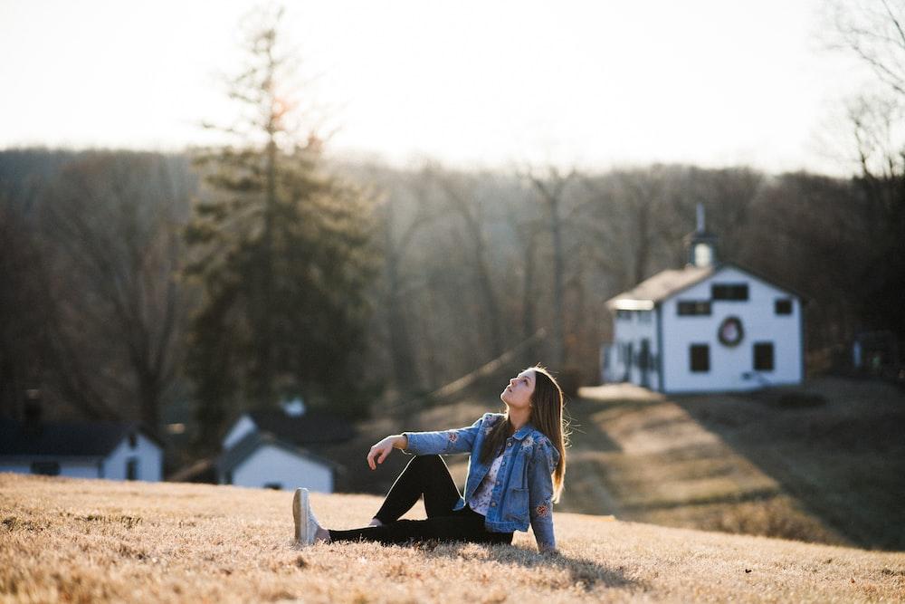 woman in blue denim jacket sitting on brown dirt during daytime