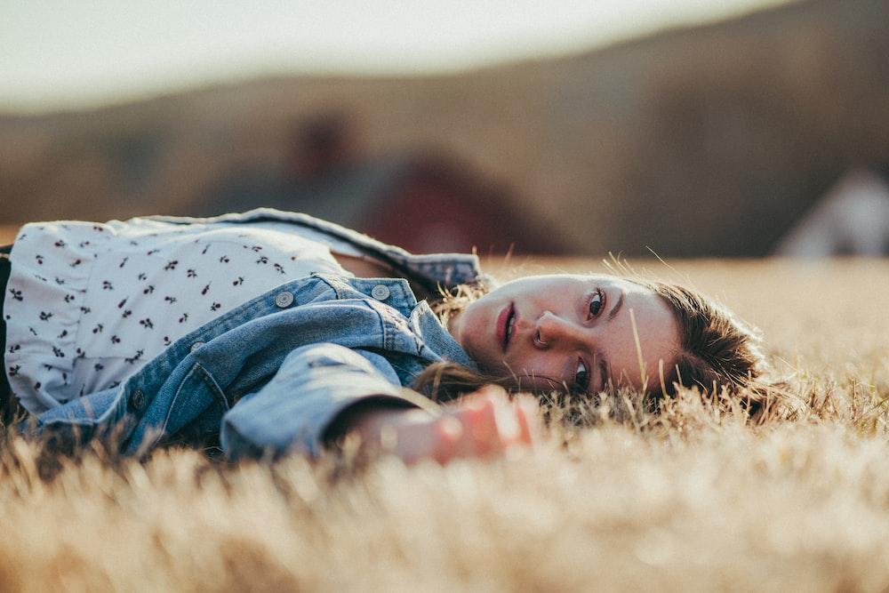 boy in blue denim jacket lying on brown grass field during daytime
