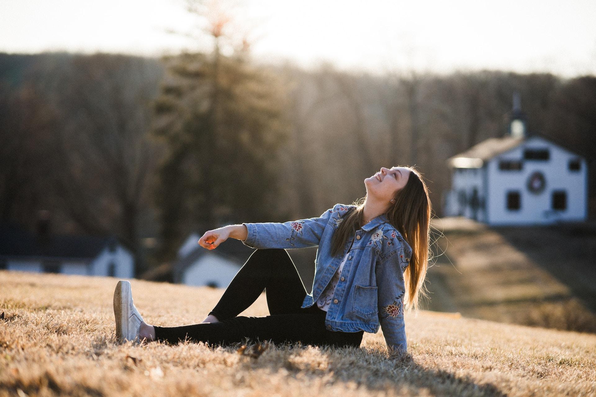woman in blue denim jacket sitting on brown grass during daytime