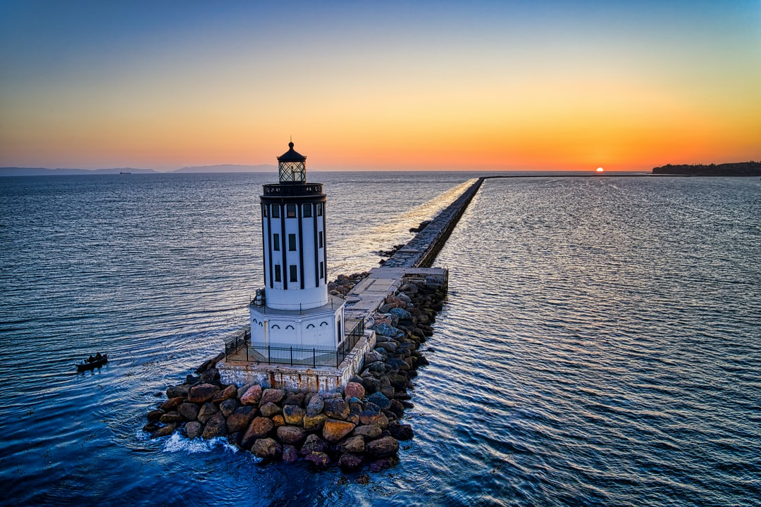A Lighthouse On A Jetty At Sunset.  - unsplash
