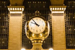 gold and white analog clock