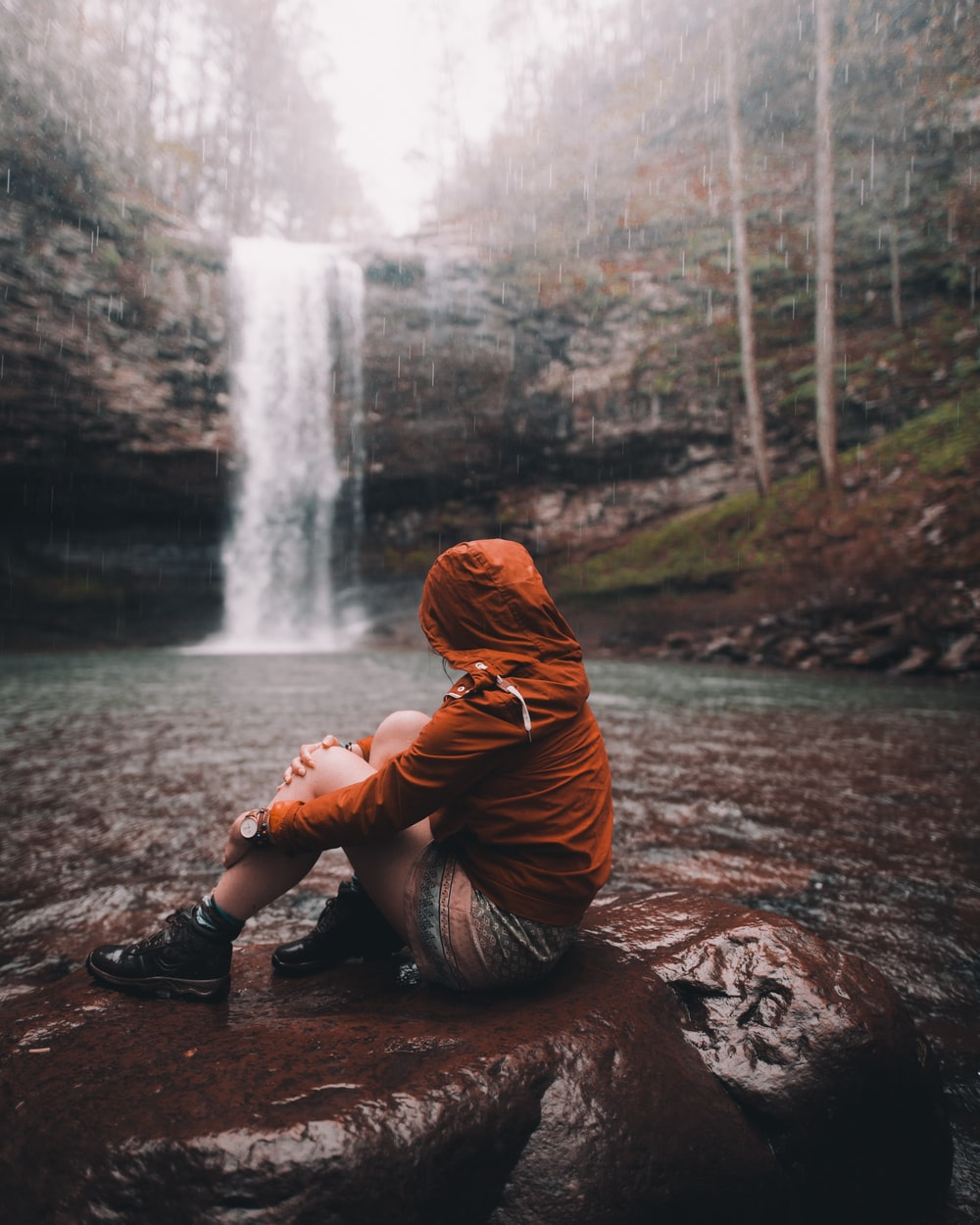 woman in brown hoodie sitting on rock near waterfalls during daytime