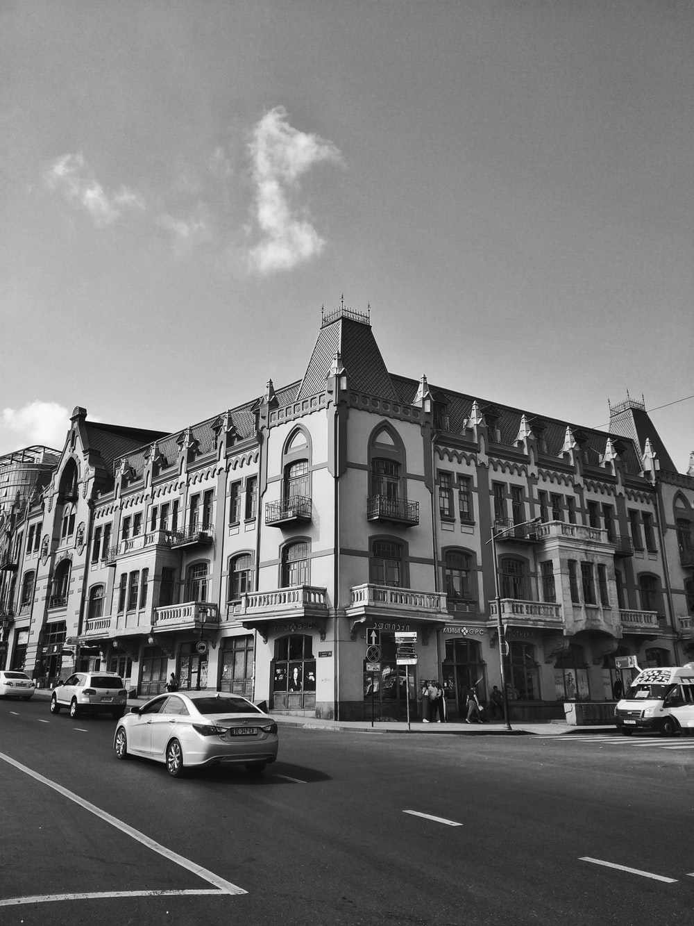 grayscale photo of cars parked beside building