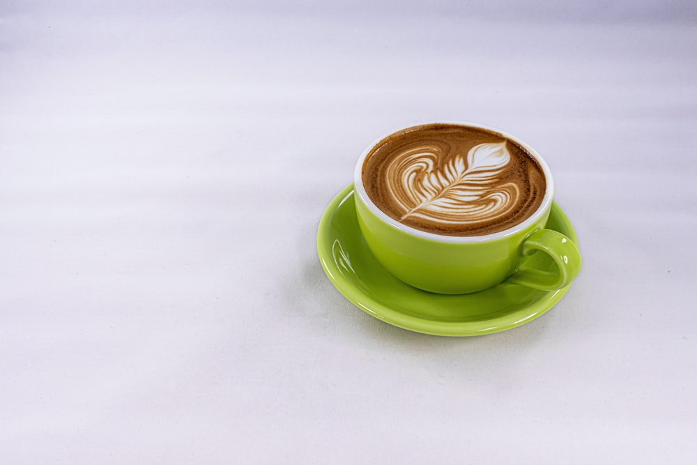 green ceramic cup with saucer