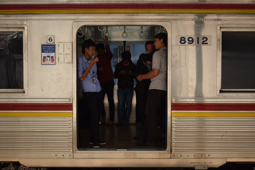 3 men and 2 women standing in front of white train