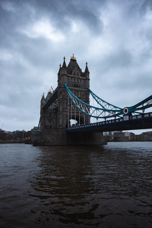 gray bridge under cloudy sky during daytime