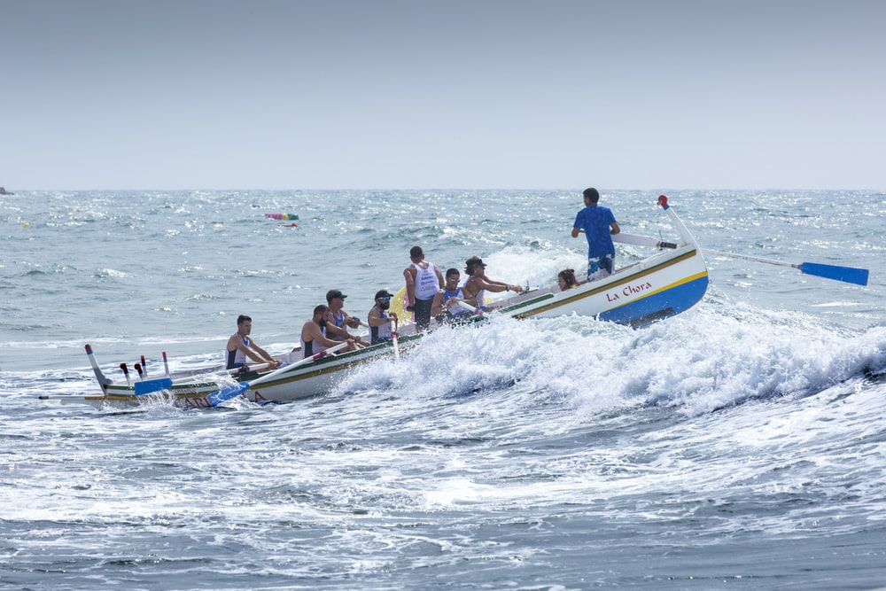 people riding on blue and yellow boat during daytime